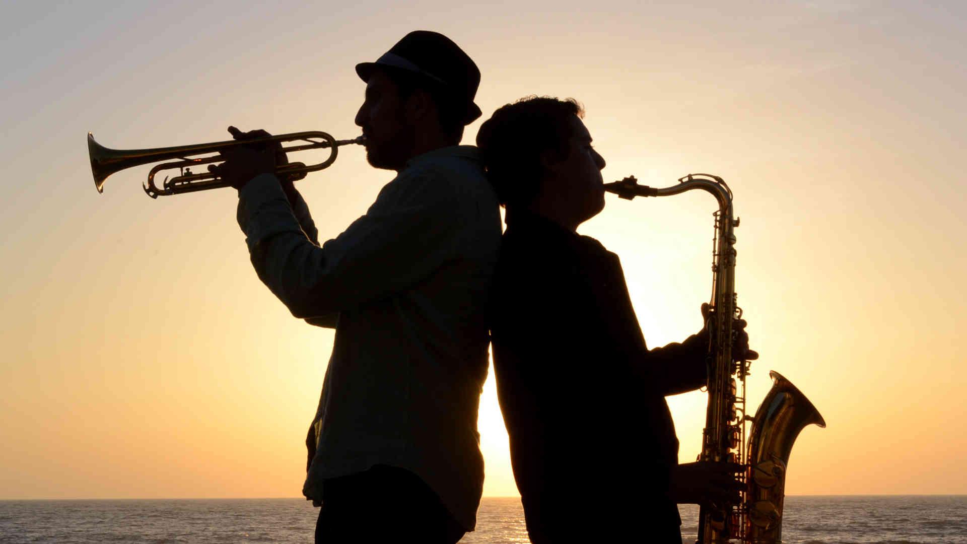Grupo musical en la playa, silueta - fotografía profesional