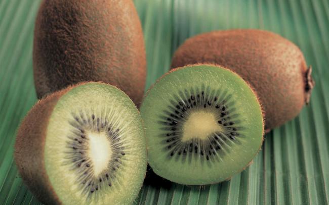 Fotografía de kiwi con fondo de planta.