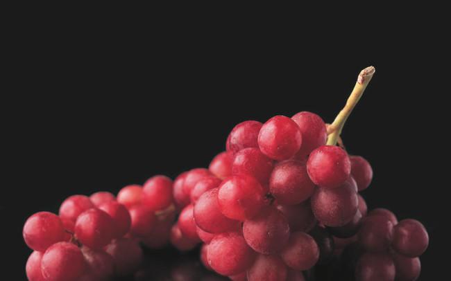 Fotografía de uvas con fondo negro