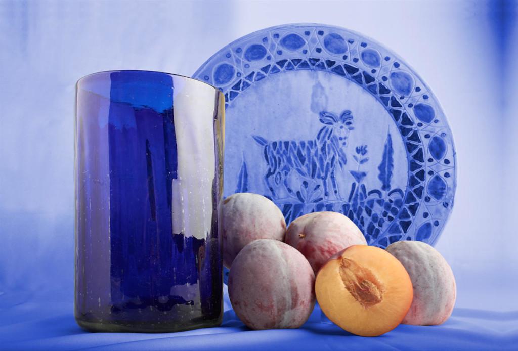 Fotografía de durazno con fondo, plato, y florero azul.