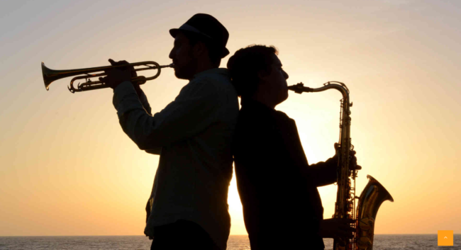 Músicos delante del sol, en contraluz, trompeta y saxofón